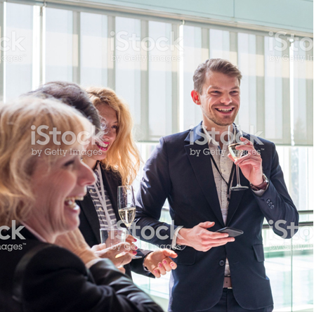 Four business professionals laughing and drinking champagne.
