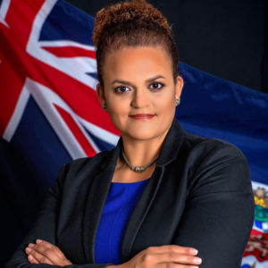 Photo of Financial Services Minister Tara Rivers, smiling in front of the Cayman Islands flag.