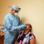 Photo of a doctor giving a patient a COVID nasal swab test.