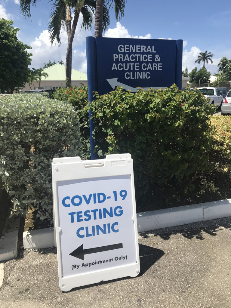 "Photo of a sign outside stating ""COVID testing clinic, (appointment only)"" with an arrow pointing towards the clinic."