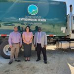 3 business professionals lined up outside a Department of Environmental Health truck.